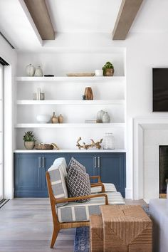 White floating shelves over blue built-in cabinets display fine pottery and deco… White floating shelves over blue built-in cabinets display fine pottery and decor in a cottage living room beside a white beveled fireplace. Cottage Living Rooms, Coastal Living Rooms, Home Living Room, Living Room Decor, Coastal Cottage, Coastal Homes, Coastal Decor, Built In Shelves Living Room, Living Room Cabinets