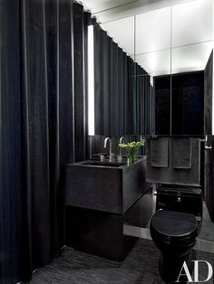 The vanity is granite, and the black towels are by Calvin Klein Home   archdigest.com