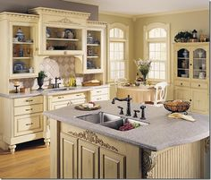 This is such a pretty kitchen. I love how the sink is hidden and the curved edges of the counters! And the use of old style cabinets.