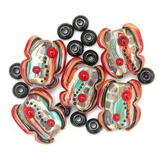 These beads have bases in violet, topped with shades of turquoise, pale yellow, coral and red, with reactive 'Multicolor' glass, streaks of silvered ivory and sparkling goldstone. The beads are decorated with bubble dots in red and trails of small black dots. They are framed with black, coral and transparent red-orange.