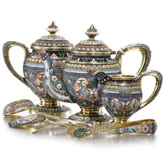 A SILVER-GILT AND CLOISONNÉ ENAMEL TEASET, 11TH ARTEL, MOSCOW, 1908-1917 comprising: a teapot and sugar bowl with hinged lids, creamer, sugar tongs, tea strainer, fork and tea scoop, all similarly decorated with stylised, shaded enamel foliate and geometric motifs on grey grounds, 84 standard Quantity: 7 height of teapot: 14cm, 5 1/2 in.