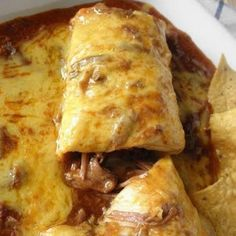 Smothered Beef Burrito.  Alternate Pork instructions: Put pork in the slow cooker on low for about 7 hours with a can of enchilada sauce, pull out pork with a slotted spoon and shred with a cake mixer for fast shredding,  fill tortillas with meat and a little bit of juice (you can add rice, beans, onions, etc to your liking), roll burrito and place on oven safe dish, add more juice and shredded cheese, bake until melted, add more juice if desired. Serve with Rice, beans, chips, salsa. Enjoy!