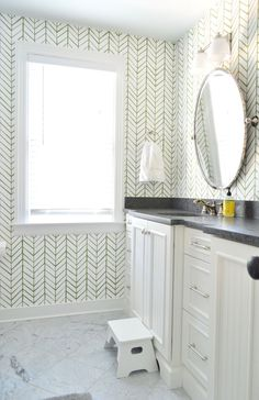 Crisp all-white bathroom with gray countertops and chevron patterned pencil tiles on the walls with dark grout.