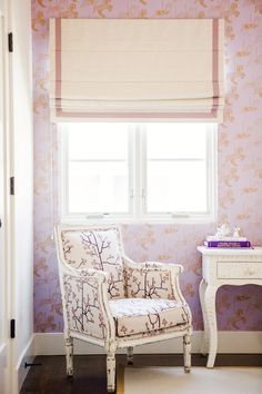 Pale pink wallpaper with slight pattern and patterned armchair in reading nook