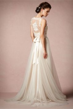 For the truly romantic, this Catherine Deane original will take your breath away. Voluminous layers of tulle waft over gleaming silk charmeuse for a full skirt. At the bodice, embroidered roses climb across a tulle trellis that frames the neckline. Side zip. From BHLDN (1,800$)