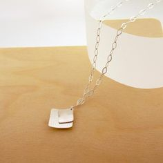 Silver necklace with a textured silver square cradling a smaller silver square