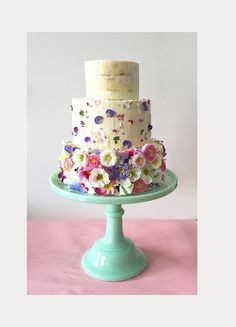 Three different style tiers work so well together.  Top tier is semi naked, middle tier has petals attached to side of cake and lower tier has whole flowers attached to the cake
