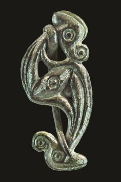 Iron Age Celtic Bronze Dragonesque Brooch    1st century BC-1st century AD . A rare type of dragonesque brooch with irregular s-curved body, discoid lobe head with elliptical ear and nose; discoid lobe tail with elliptical fins; incised ring-and-dot to head, body and tail; the body in openwork with La Tene comma-leaf elements; the pin substantial, coiled around the neck and looped over the upper tail.