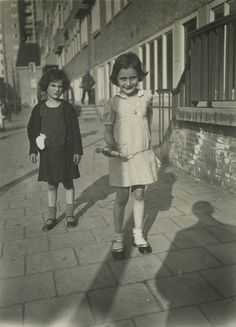 Anne Frank holding a jumping rope next to her friend, Sanne Ledermann, on a sidewalk in Merwedeplein, Amsterdam .