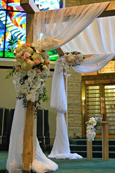 Our wooden framed Chuppah draped in white gauze. Tied back with pink roses, stock, ruscus and phalenopsis orchids.