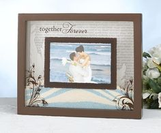 "Wedding Unity Sand Ceremony Frame features a painted brown frame.  The inside back is engraved with various terms of endearment and a leafy design on both sides. There are two panes of glass. One is secured to the frame and is designed to hold the sand in place. The other pane of glass is in front and is designed to hold your photo. It is painted with the words ""Together Forever,"" leafy designs at the bottom corners and a border in the middle. The lid slides outward so you can fill it with…"