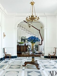 Ceramic pitchers by Picasso are displayed atop a Regency table in the entrance hall | archdigest.com