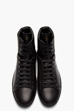 SAINT LAURENT //  Black Classic Leather high-Top sneakers  31418M050001  High top leather sneakers in black. Round toe. Black lace up closure with black eyelets. Logo print at tongue in gold. Paneled upper with padding at collar and heel. Embossed logo at heel collar. Black rubber foxing. Tone on tone stitching. Leather upper, rubber sole. Made in Italy.  $590 CAD