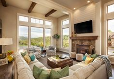 The L-shaped couch forms the boundaries of this living room, and contains the space. A stone fireplace is featured across from the couch, and contrasts the white walls and furniture, along with the leather ottoman and stained wood floor.