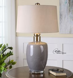 Uttermost Ovidius Lamp. Ceramic base finished in a crackle gray glaze accented with brushed nickel plated details and a crystal foot. The tapered round hardback shade is an oatmeal linen fabric with light slubbing. Due to the nature of fired glazes on ceramic lamps, finishes wil