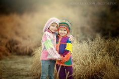 Sisters holding hands and posing for portrait near Ahwatukee in bright colored handmade sweaters and hats