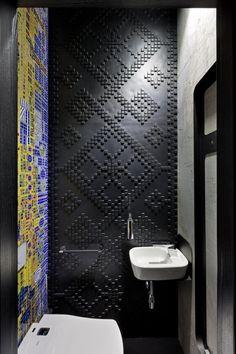 Decorative black tiles with a pattern have been paired with brightly colored tiles in this bathroom.
