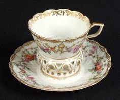 MEISSEN TREMBLEUSE CUP AND SAUCER. Meissen porcelain trembleuse cup and saucer, gilt border with polychrome hand painted floral swags. Marked: Crossed swords mark above H.