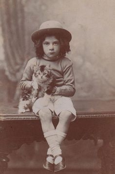 Adorable vintage photo of little boy holding his kitten.