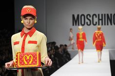 "American fashion designer Jeremy Scott presented his first collection for Italian label Moschino yesterday during Milan Fashion Week. And he really bought some quintessentially American flavor with him: many of the clothes were inspired by McDonalds. Let's call it ""McSchino."" It's amazing. Models walked the runway in '80s-style looks in the fast food chain's color scheme and featuring its logo, slightly modified into Moschino's signature heart shape motif."