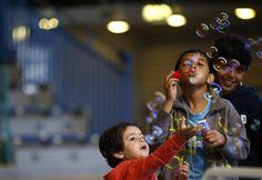 Crianças brincam com bolhas de sabão em abrigo temporário de Hanau, na…