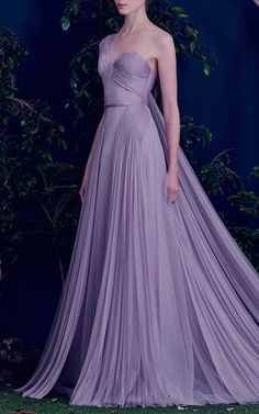 This **Hamda Al Fahim** gown is crafted of hand-pleated tulle that drapes across the hips in an asymmetrical design, as well as a pleated shoulder panel that cascades down. It features a pleated bodice, layers of lavender tulle, mixing dotted tulle with sheer lavender layers.
