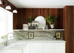dark panelling and white cabinets/marble
