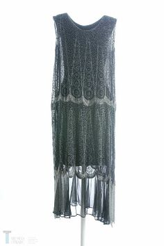 Ca. 1920. Mid calf length dress in black gauze with a rounded neckline, sleeveless with dropped waist and a wide frill at the hem. Embroidered decoration with transparent glass bugles of different sizes which form the background of a labyrinth in vertical rows. Remarkable silver wavy lines at the hip and hem. The embroidery was applied after the garment was made up. Museo del Traje. CIPE