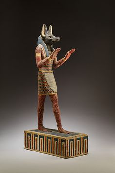 Statuette of Anubis  Period:Ptolemaic Period Date:332–30 B.C. Geography:From Egypt Medium:Plastered and painted wood Dimensions:H. 42.3 cm (16 5/8 in.); W. 10.1 cm (4 in.); D. 20.7 cm (8 1/8 in.). Statuette of Anubis | Ptolemaic Period | The Met