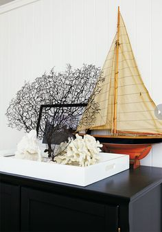 Home decor accents: model schooner and ocean coral keep the room beachy without being predictable.