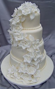 A mixture of sugar roses & calla lilies on a cascading drape. ivory icing sets off white flowers. Remember that sponge cakes with Butter cream at the height of summer in this style of cake no matter how strong the supporting dowels are not always the wisest choice