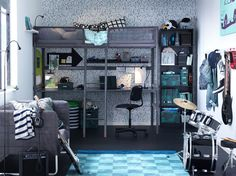 A loft bed with desk underneath and drum kit in a blue, dark gray and silver children's bedroom.