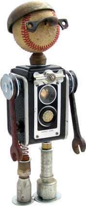"""Name: BuntzD.O.B.: 10/14/11Height: 13""""Principal Components: Camera, baseball, sash lock, telephone bell, buttons, spring, wrenches, hydraulic fittings"""