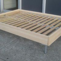 Un Varnish Wooden Bed Frame Using Grey And White Bedding Placed On