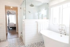 Cottage bathroom features a glass and shiplap shower enclosure fitted with a ceiling mount rain shower head positioned next to a freestanding tub and vintage style tub filler atop a white and blue mosaic tiled floor. Bad Inspiration, Bathroom Inspiration, Bathroom Ideas, Bathroom Showers, Bathroom Trends, Bathroom Designs, Glass Showers, Shower Designs, Shower Tub