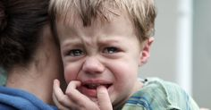 crying upset boy being held by parent