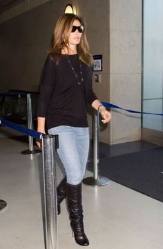 Travel style: Cindy Crawford rocks the simple rockstar style: black loose fitted blouse over a pair of denim, black boots, black shades and an oversized bead necklace. You cannot not look together in this simple style. The trick is really to travel only in matching, neutral colors that are wrinkle-free - preferably opt for a couple stand-outish pieces in luxury materials such as cashmere, leather or silk to add that air of grace to it.