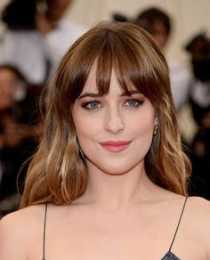 Dakota Johnson - warm brown shadow emphasizes her blue eyes. Rose gold lips and softly sculpted cheeks with strong brows finish the look.