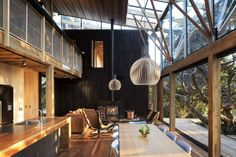 Love all the natural light!  And the wood stove looks cozy - Under Pohutukawa by Herbst Architects
