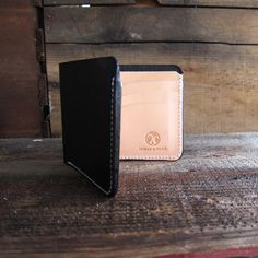 Our take on the classic men's leather wallet. This billfold combines smooth and strong black English bridle leather with natural vegetable tanned leather for a truly timeless feel. This handmade leath