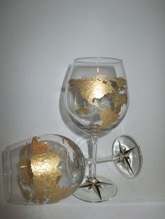 Hand painted wine glasses representing a map of the world, complete with a compass at the base. These can be personalized in alternate colors(or