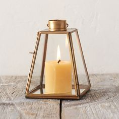 """Framed in antiqued brass, this petite lantern with a polished, pyramid shape and loop for hanging brings light wherever it goes.- Brass, glass- Gently wipe clean with soft, dry cloth- For use with tea lights only- Indoor or sheltered outdoor use- Opening: 1.25"""" diameter- Imported5.5""""H, 4""""W at base, 2.5""""W at top, 5""""DHanging loop: 1""""H"""