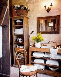 Natural wood, rugged plaster walls, and antique furnishings adapted for the bath conjure the ambience of a Tuscan farmhouse and also offer a way to minimize the appearance of fixtures.