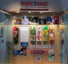 """The 2013 Boards + Bands display at The GRAMMY Museum in Los Angeles, with the late addition of Guy Mariano's board with lyrics to """"Pursuit Of Happiness"""" by Kid Cudi, plus signatures by Guy, Cudi, and Lissie (whose version of the song accompanies Guy's skate segment in the Girl Skateboards film """"Pretty Sweet"""")."""