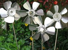 Metal flowers made from small fan blades, galvanized cages, and drawer knobs.