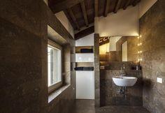 Estetica più contemporanea per le stanze da bagno poste al primo piano, realizzate in travertino noce