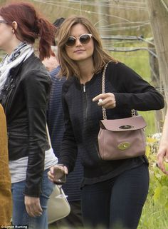 All black: The brunette beauty wore a dark zipped up sweater teamed with matching fitted trousers