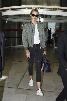 Karlie Kloss en el aeropuerto de Los Ángeles. Con jeans cropped negros, de Re/Done; camiseta blanca básica, bomber verde, de Unravel; bolso de Versace y zapatillas de adidas