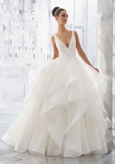 "Light and Airy, this Stunning Flounced Organza Ball Gown with Wide Horsehair Edging Features a Plunging V-Neck and Open V-Back. Illusion Insets Along Sides . Available in Three Lengths: 55"", 58"", 61"". Colors Available: White, Ivory, Ivory/Stripe. Shown in Ivory, and Ivory Stripe."