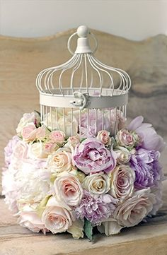 Cream bird-cage filled with pastel roses.